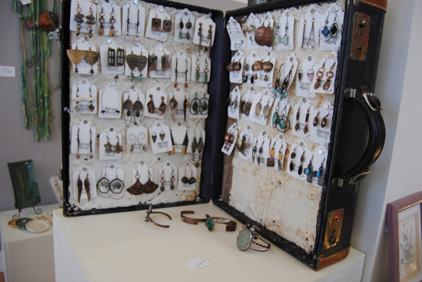 I just love the way Sarah displays her pieces. This is an old suitcase that is lined with barn metal and she uses magnets to hold her earrings in place.